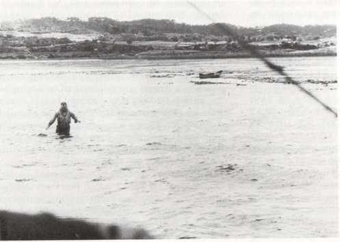 Lieutenant Fox wading towards his rescue aircraft on 29 March 1945.