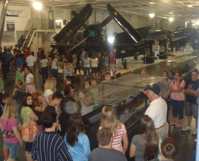 Volunteer Ed Walker leads a tour for a school group in Hangar Bay 2.