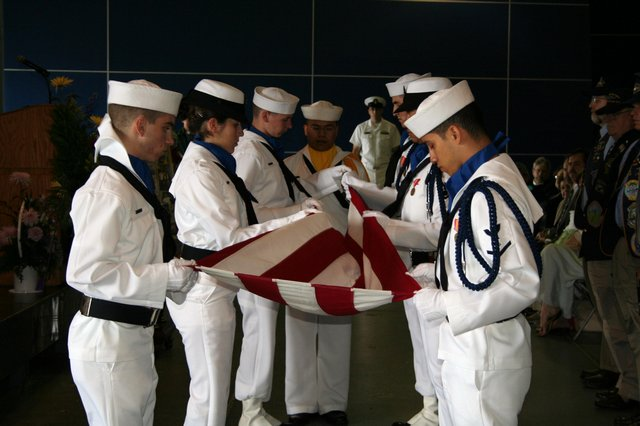 United States Navy color guard folds the colors for presentation to Mrs. Nuzum.