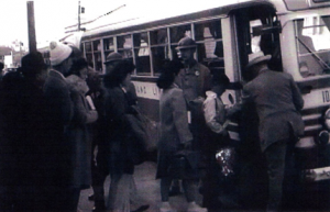 This image, taken from a government news reel, shows Mary Murakami (third in line) boarding the buss from San Francisco to Tanforan Assembly Center.